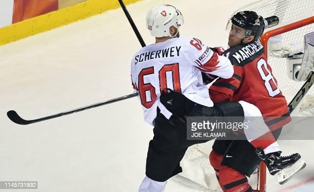 Switzerland's forward Tristan Scherwey and Canada's forward Jonathan Marchessault vie for the puck during the IIHF Men's Ice Hockey World...