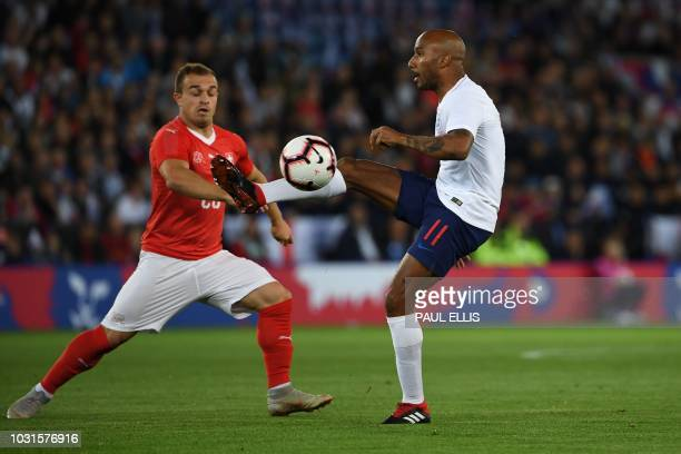 Switzerland's forward Xherdan Shaqiri vies with England's midfielder Fabian Delph during a friendly international football match between England and...