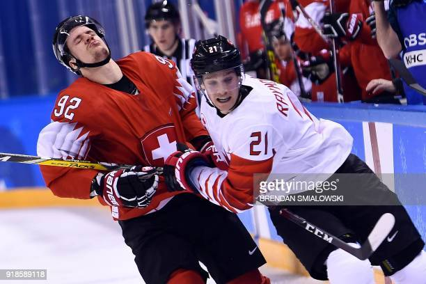 Switzerland's Gaetan Haas and Canada's Mason Raymond clash in the men's preliminary round ice hockey match between Switzerland and Canada during the...