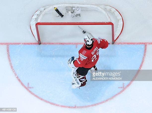 Switzerland's goalie Reto Berra gets the puck out of his net during a IIHF International Ice Hockey World Championship preliminary round group B game...