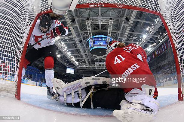 Switzerland's goalkeeper Florence Schelling vies with Canada's Natalie Spooner during the Women's Ice Hockey semifinal match Canada vs Switzerland at...
