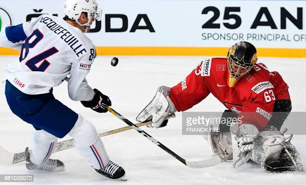 Switzerland's goalkeeper Leonardo Genoni stops a puck from France's defender Kevin Hecquefeuille during the IIHF Men's World Championship group B ice...
