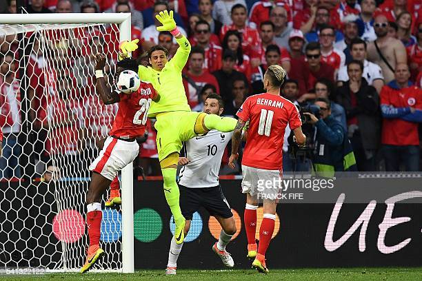 Switzerland's goalkeeper Yann Sommer jumps for the ball as France's forward AndrePierre Gignac looks on during the Euro 2016 group A football match...