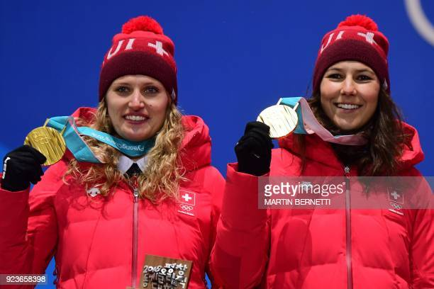 Switzerland's gold medallists Denise Feierabend and Wendy Holdener pose on the podium during the medal ceremony for the alpine skiing team event at...