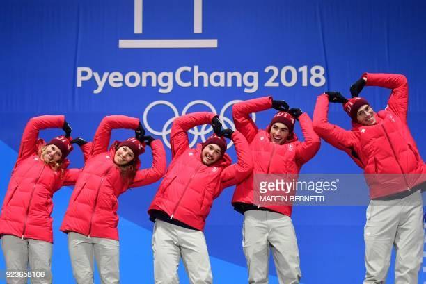 TOPSHOT Switzerland's gold medallists Denise Feierabend Wendy Holdener Luca Aerni Daniel Yule and Ramon Zenhaeusern make heart shapes on the podium...