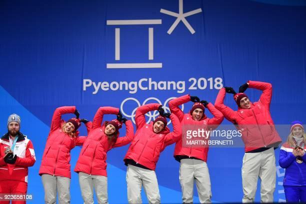 Switzerland's gold medallists Denise Feierabend Wendy Holdener Luca Aerni Daniel Yule and Ramon Zenhaeusern make heart shapes on the podium during...