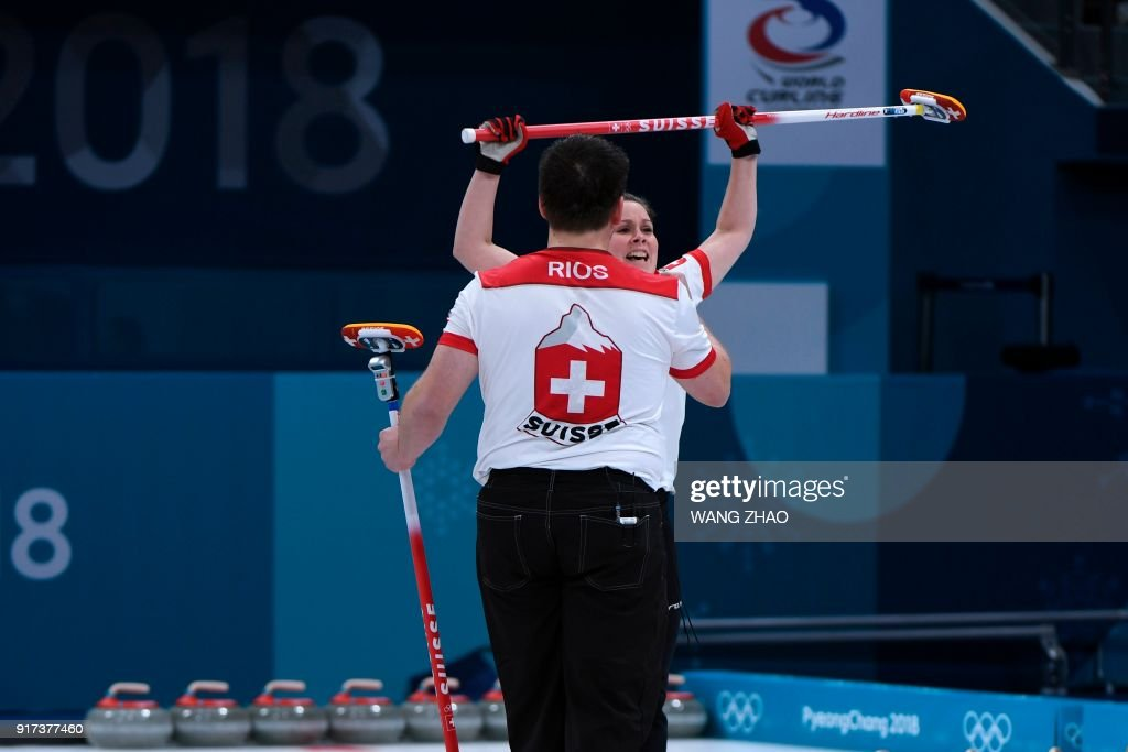 Switzerland's Jenny Perret (R) celebrates after winning the curling mixed doubles semi-final during the Pyeongchang 2018 Winter Olympic Games at the Gangneung Curling Centre in Gangneung on February 12, 2018. / AFP PHOTO / WANG Zhao