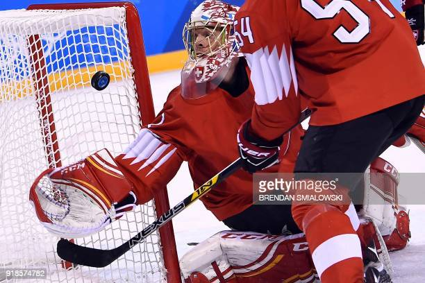 Switzerland's Jonas Hiller stops a puck in the men's preliminary round ice hockey match between Switzerland and Canada during the Pyeongchang 2018...