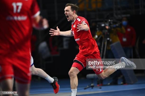 Switzerland's left wing Marvin Lier celebrates after scoring during the 2021 World Men's Handball Championship between Group III teams Switzerland...