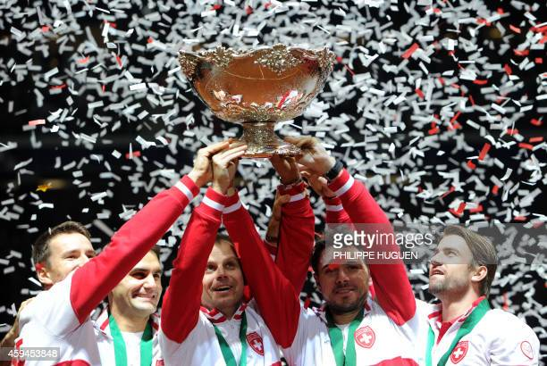 Switzerland's Marco Chiudinelli, Roger Federer, Davis Cup team captain Severin Luthi, Stanislas Wawrinka and Michael Lammer celebrate with the trophy...