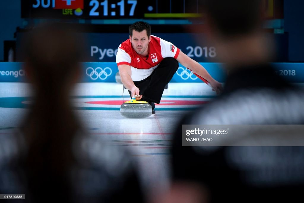Switzerland's Martin Rios pushes the stone during the curling mixed doubles semi-final during the Pyeongchang 2018 Winter Olympic Games at the Gangneung Curling Centre in Gangneung on February 12, 2018. / AFP PHOTO / WANG Zhao
