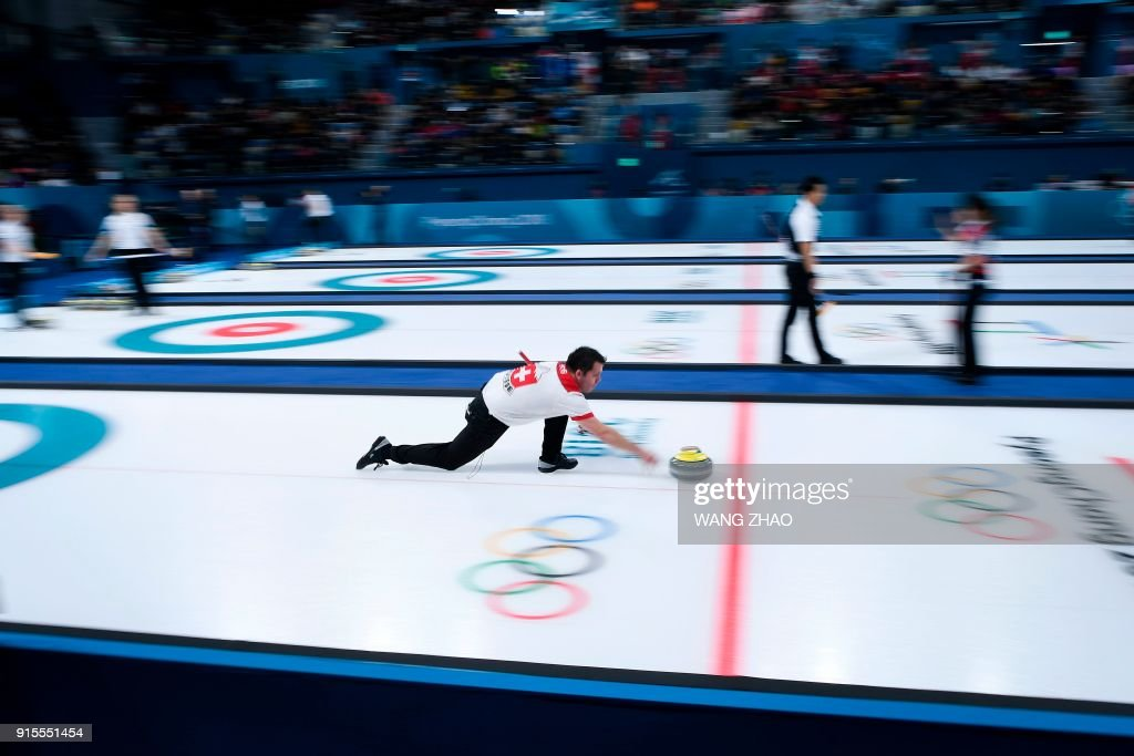 Switzerland's Martin Rios throws the stone during the curling mixed doubles round robin session between China and Switzerland during the Pyeongchang 2018 Winter Olympic Games at the Gangneung Curling Centre in Gangneung on February 8, 2018. / AFP PHOTO / WANG Zhao