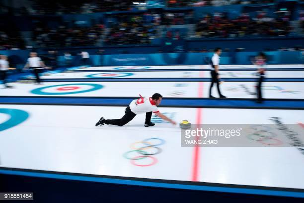 Switzerland's Martin Rios throws the stone during the curling mixed doubles round robin session between China and Switzerland during the Pyeongchang...