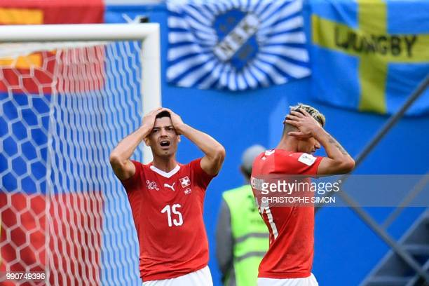 Switzerland's midfielder Blerim Dzemaili and Switzerland's midfielder Valon Behrami react after missing a goal opportunity during the Russia 2018...