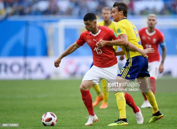 Switzerland's midfielder Blerim Dzemaili challenges Sweden's midfielder Albin Ekdal during the Russia 2018 World Cup round of 16 football match...