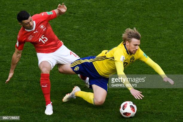 Switzerland's midfielder Blerim Dzemaili fights for the ball with Sweden's midfielder Emil Forsberg during the Russia 2018 World Cup round of 16...