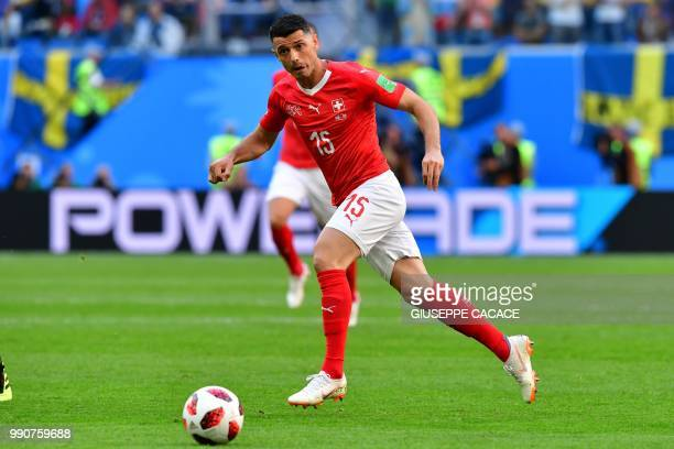 Switzerland's midfielder Blerim Dzemaili runs with the ball during the Russia 2018 World Cup round of 16 football match between Sweden and...