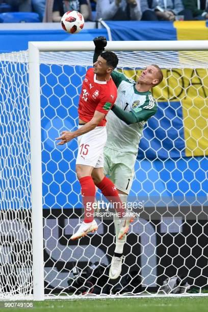 Switzerland's midfielder Blerim Dzemaili vies with Sweden's goalkeeper Robin Olsen during the Russia 2018 World Cup round of 16 football match...