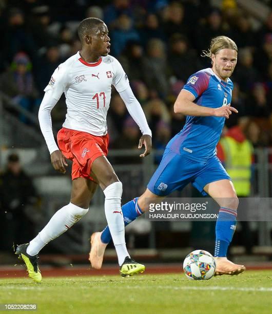 Switzerland's midfielder Denis Zakaria and Iceland's midfielder Birkir Bjarnason vie for the ball during the UEFA Nations League Group Stage football...