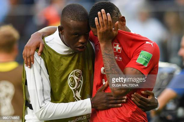 Switzerland's midfielder Gelson Fernandes comforts defender Manuel Akanji after the team lost the Russia 2018 World Cup round of 16 football match...