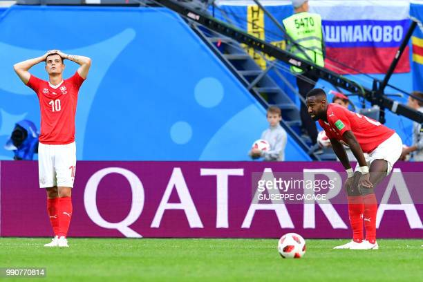 Switzerland's midfielder Granit Xhaka and defender Johan Djourou react after losing the Russia 2018 World Cup round of 16 football match between...