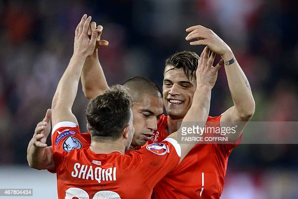 Switzerland's midfielder Granit Xhaka celebrates with teammates midfielder Xherdan Shaqiri and midfielder Gokhan Inler after he scored the team's...