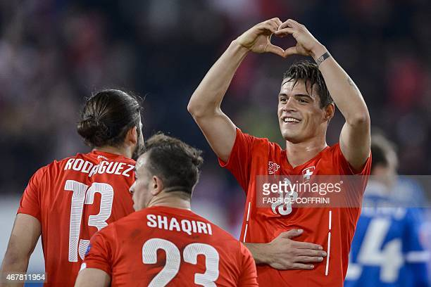Switzerland's midfielder Granit Xhaka celebrates with teammates Ricardo Rodriguez and Xherdan Shaqiri after scoring his team's second goal during the...