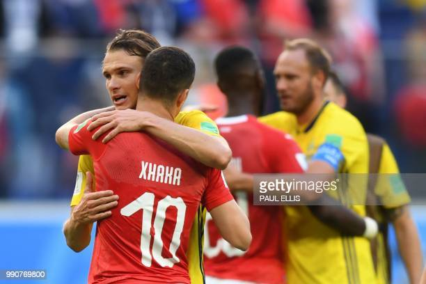 Switzerland's midfielder Granit Xhaka is comforted by Sweden's midfielder Albin Ekdal at the end of the Russia 2018 World Cup round of 16 football...