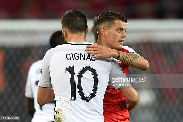Switzerland's midfielder Granit Xhaka pats France's forward AndrePierre Gignac on the back following their 00 draw in the Euro 2016 group A football...