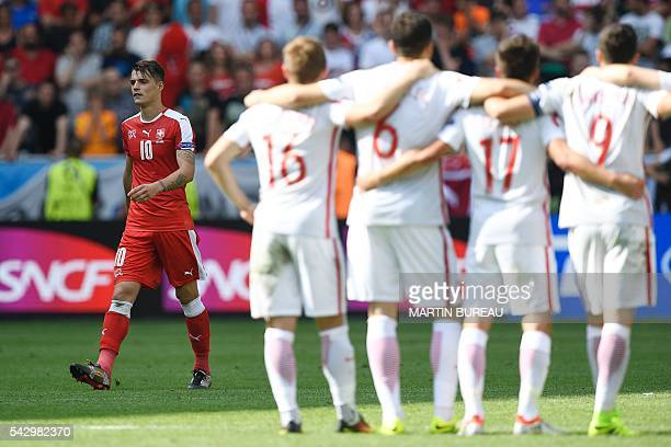 Switzerland's midfielder Granit Xhaka reacts after missing a penalty during the Euro 2016 round of sixteen football match Switzerland vs Poland on...