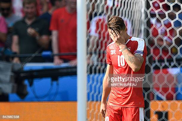 Switzerland's midfielder Granit Xhaka reacts after missing his attempt during the penalty shootout during the Euro 2016 round of sixteen football...