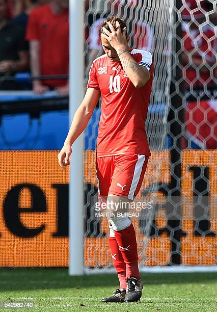 Switzerland's midfielder Granit Xhaka reacts after missing his penalty during the Euro 2016 round of sixteen football match Switzerland vs Poland on...