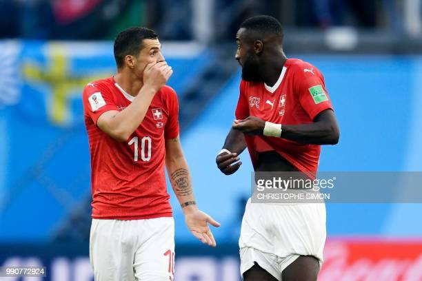 Switzerland's midfielder Granit Xhaka speaks to Switzerland's defender Johan Djourou at the end of the Russia 2018 World Cup round of 16 football...