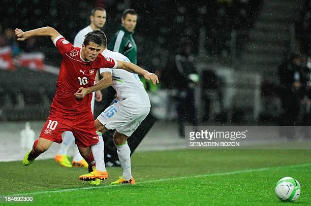 Switzerland's midfielder Granit Xhaka vies with Slovenia's defender Andraz Struna during the world cup 2014 qualifying football match Switzerland vs...