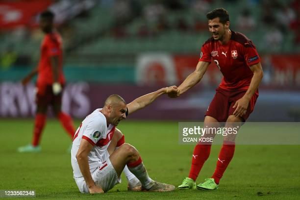 Switzerland's midfielder Remo Freuler helps Turkey's forward Burak Yilmaz up during the UEFA EURO 2020 Group A football match between Switzerland and...