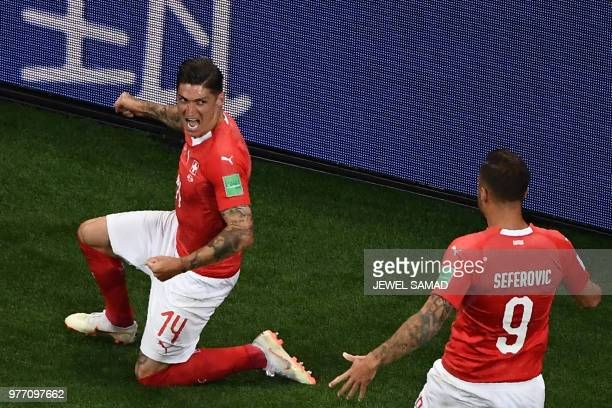 Switzerland's midfielder Steven Zuber celebrates with teammates after scoring during the Russia 2018 World Cup Group E football match between Brazil...
