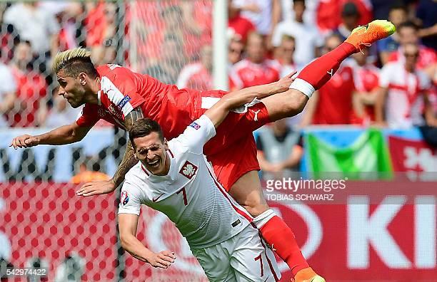 TOPSHOT Switzerland's midfielder Valon Behrami vies for the header with Poland's forward Arkadiusz Milik during the Euro 2016 round of sixteen...