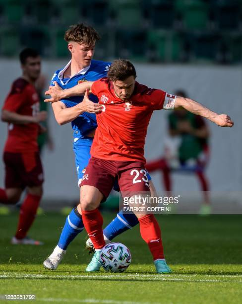 Switzerland's midfielder Xherdan Shaqiri and Liechtenstein's midfielder Noah Frick fight for the ball during a friendly football match between...