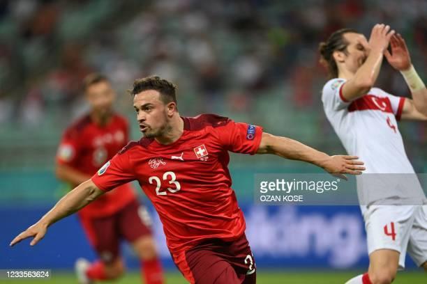 Switzerland's midfielder Xherdan Shaqiri celebrates scoring his team's third goal as Turkey's defender Caglar Soyuncu reacts during the UEFA EURO...