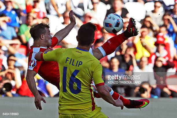 Switzerland's midfielder Xherdan Shaqiri kicks the ball in front of Romania's defender Steliano Filip during the Euro 2016 group A football match...