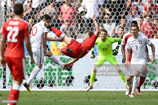 TOPSHOT Switzerland's midfielder Xherdan Shaqiri shoots to score his team's equalising goal during the Euro 2016 round of sixteen football match...