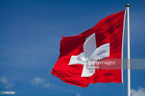 switzerland's national flag flying - switzerland stock pictures, royalty-free photos & images