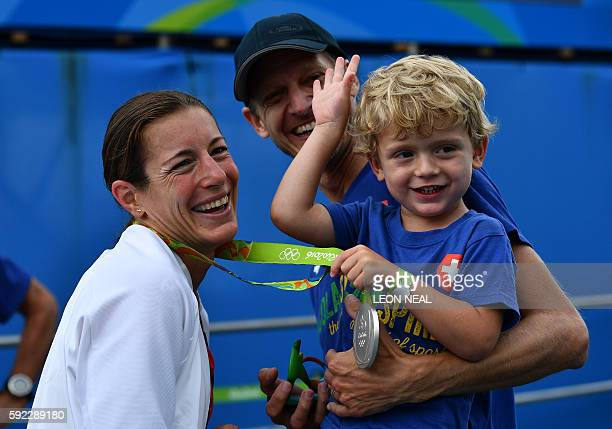 Switzerland's Nicola Spirig celebrates with her family after receiving the silver medal in the women's triathlon at Fort Copacabana during the Rio...
