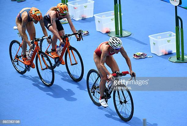 Switzerland's Nicola Spirig rides ahead of athletes competing in the cycling portion of the women's triathlon at Fort Copacabana during the Rio 2016...