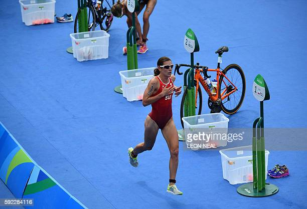 Switzerland's Nicola Spirig runs in the transition area from the cycling to the running portion of the women's triathlon at Fort Copacabana during...