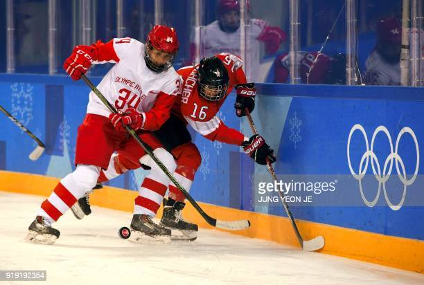 Switzerland's Nina Waidacher and Russia's Svetlana Tkachyova fight for the puck in the women's quarter-final ice hockey match between the Olympic...