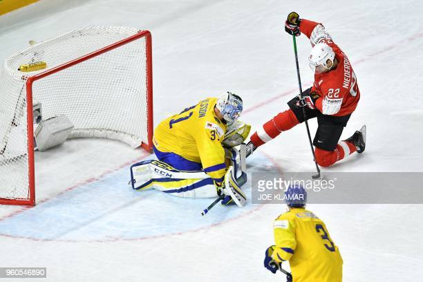 Switzerland's Nino Niederreiter and Sweden's goalkeeper Anders Nilsson vie during the final match Sweden vs Switzerland of the 2018 IIHF Ice Hockey...