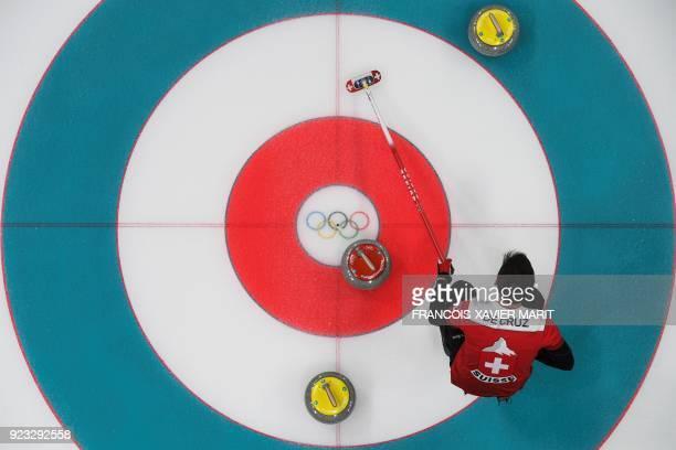 Switzerland's Peter De Cruz brushes the ice during the curling men's bronze medal game between Canada and Switzerland during the Pyeongchang 2018...