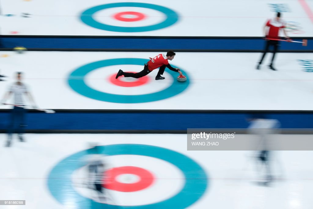 TOPSHOT - Switzerland's Peter De Cruz throws the stone during the curling men's round robin session between Switzerland and Italy during the Pyeongchang 2018 Winter Olympic Games at the Gangneung Curling Centre in Gangneung on February 14, 2018. / AFP PHOTO / WANG Zhao