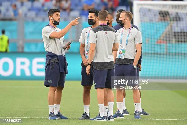 Switzerland's players inspect the pitch ahead of the UEFA EURO 2020 Group A football match between Italy and Switzerland at the Olympic Stadium in...